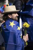 Un uomo con un fiore e una bandiera di Europa fotografia stock