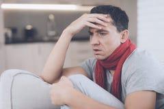 Un uomo con un freddo si siede sullo strato, nascondentesi dietro una coperta rossa Ha un'emicrania Fotografie Stock