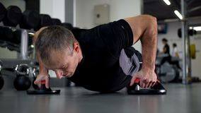Un uomo con i bei muscoli estorti fuori dal pavimento nella palestra 4K Mo lento stock footage