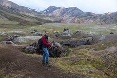 Un uomo con i pali di trekking attraversa through le montagne immagini stock