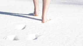 Un uomo con i piedi nudi passa attraverso la neve sciolta video d archivio