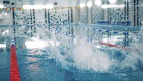 Un uomo con i salti bionici in uno stagno, allenamento di nuoto della gamba archivi video