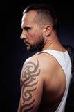 Un uomo con i tatuaggi sulle sue armi Siluetta dell'ente muscolare tipo brutale caucasico dei pantaloni a vita bassa con taglio d Fotografia Stock