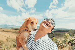 Un uomo con il cane Montagna e cielo blu e nuvole molto piacevoli fotografia stock
