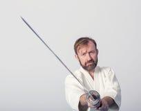 Un uomo con il katana su pratica di Iaido Immagini Stock