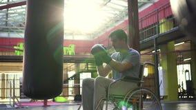 Un uomo con un'inabilità in una sedia a rotelle batte un punching ball con i guanti nella palestra archivi video