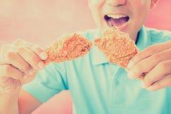 Un uomo con la bocca di apertura circa da mangiare ha fritto nel grasso bollente le coscie di pollo Fotografia Stock Libera da Diritti