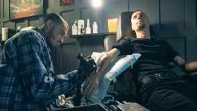 Un uomo con la mano artificiale sta ottenendo un tatuaggio archivi video