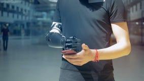Un uomo con la mano prostetica bionica, esaminante il suo telefono archivi video
