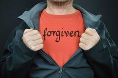 Un uomo con la parola perdonata sulla sua maglietta immagine stock