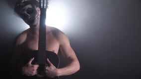Un uomo con la pittura nuda del fronte e del torso da Santa Muerte sta tenendo una chitarra video d archivio