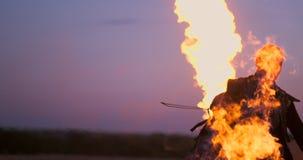 Un uomo con un lanciafiamme al tramonto al rallentatore Costume per l'apocalisse e Halloween dello zombie stock footage
