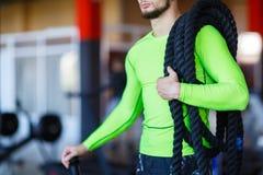 Un uomo con le corde pesanti sulle sue spalle fotografie stock