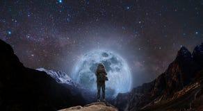 Un uomo con lo zaino che sta sul picco di montagna alla notte e montagna della siluetta con la luna piena ed il cielo luminosi in Fotografie Stock Libere da Diritti