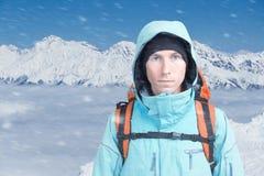 Un uomo con lo zaino nell'inverno le montagne nevose Lo scalatore sta sopra le nuvole Fotografia Stock