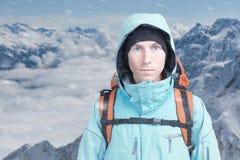 Un uomo con lo zaino nell'inverno le montagne nevose Lo scalatore sta sopra le nuvole Immagine Stock Libera da Diritti