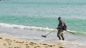 Un uomo con un metal detector sta cercando le cose importanti sulla spiaggia stock footage