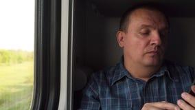 Un uomo con un telefono dalla finestra nel treno stock footage