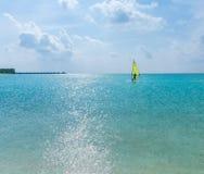 Un uomo con un bordo per fare windsurf, Maldive Fotografia Stock