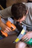 Un uomo con un cacciavite e un regolatore per erba Fotografia Stock