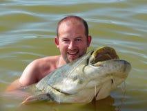 Un uomo con un pesce gatto fotografia stock
