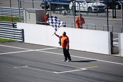 Un uomo con una bandiera a quadretti sulla corsa bikes la pista Immagini Stock