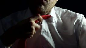 Un uomo con una barba in una camicia bianca scioglie nervoso un legame intorno al suo collo, il primo piano, il problema, fondo archivi video