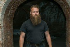 Un uomo con una barba, contro un arco del mattone fotografie stock