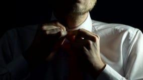 Un uomo con una barba ed in una camicia bianca sta legando il suo legame e sta abbottonando la sua camicia, il primo piano, fondo video d archivio