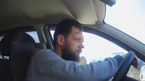 Un uomo con una barba esce dell'automobile stock footage