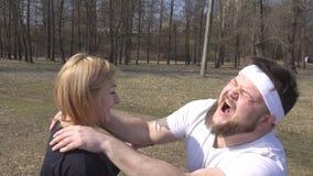 Un uomo con una barba sta provando a stare su un bordo con i chiodi per yoga con l'aiuto di un istruttore della ragazza, inchioda archivi video