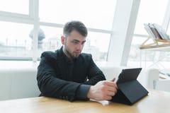 Un uomo con una barba utilizza una compressa in un bello caffè leggero Un uomo d'affari esamina la compressa un intervallo di pra immagine stock
