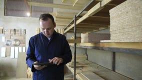 Un uomo con una compressa sta camminando in una fabbrica della mobilia e sta controllando sulla pila di legno stock footage