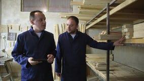 Un uomo con una compressa sta camminando in una fabbrica della mobilia e sta controllando sulla pila di legno video d archivio