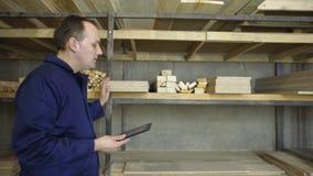 Un uomo con una compressa sta camminando in una fabbrica della mobilia e sta controllando sulla pila di legno archivi video