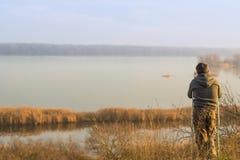 Un uomo con una gamba rotta sta stando sulla sponda del fiume Immagine Stock