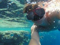Un uomo con una maschera subacquea nuota vicino ai coralli nel mare Immagini Stock Libere da Diritti