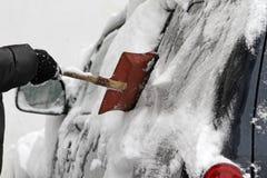 Un uomo con una pala del metallo libera l'automobile da neve sulla via dopo la grande bufera di neve nella città, tutte le automo fotografie stock