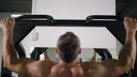 Un uomo con una parte posteriore muscolare tira su su un simulatore 4K Mo lento stock footage