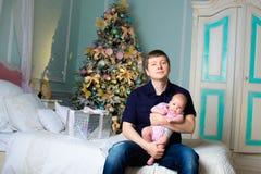 Un uomo con una piccola figlia sulle mani stanza di natale fotografia stock