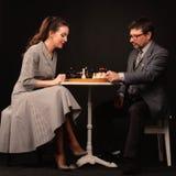 Un uomo con una ragazza gioca gli scacchi e fuma un tubo su un backgr scuro fotografia stock