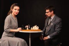 Un uomo con una ragazza gioca gli scacchi e fuma un tubo su un backgr scuro immagini stock libere da diritti