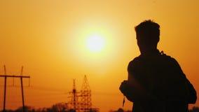 Un uomo con uno zaino dietro lui supporti contro lo sfondo del paesaggio urbano nella distanza e nel tramonto fotografie stock libere da diritti