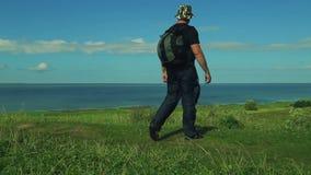 Un uomo con uno zaino dietro lui viene al bordo della montagna ed ammira la vista qui sotto Fucilazione dalla parte posteriore stock footage