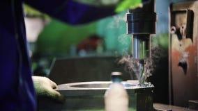Un uomo conduce il lavoro di perforazione nelle parti di metallo Ci sono trucioli del metall video d archivio