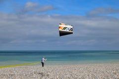 Un uomo controlla un aquilone sulle rive dell'Oceano Atlantico fotografia stock