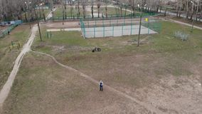 Un uomo controlla un fuco nel campo da giuoco Modo di volo automatico video d archivio