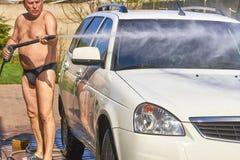 Un uomo in costume da bagno scuro sulla via lava un'automobile bianca fotografie stock libere da diritti