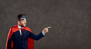 Un uomo in un costume del supereroe indica il suo dito immagine stock