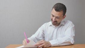 Un uomo crea un cuore su carta e sorride felicemente Immagine Stock